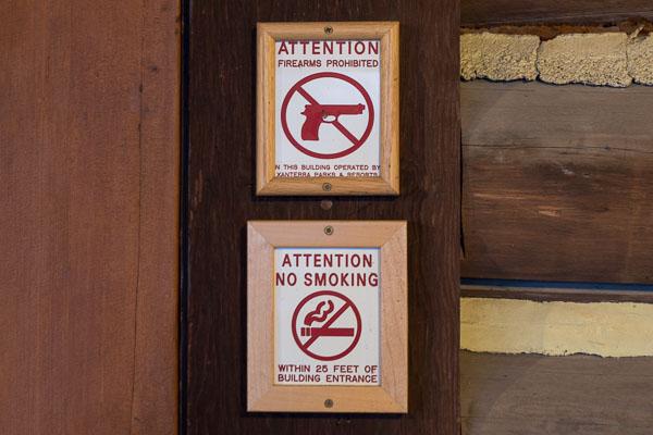 Panneaux No guns, No smoking à l'entrée d'un batiment