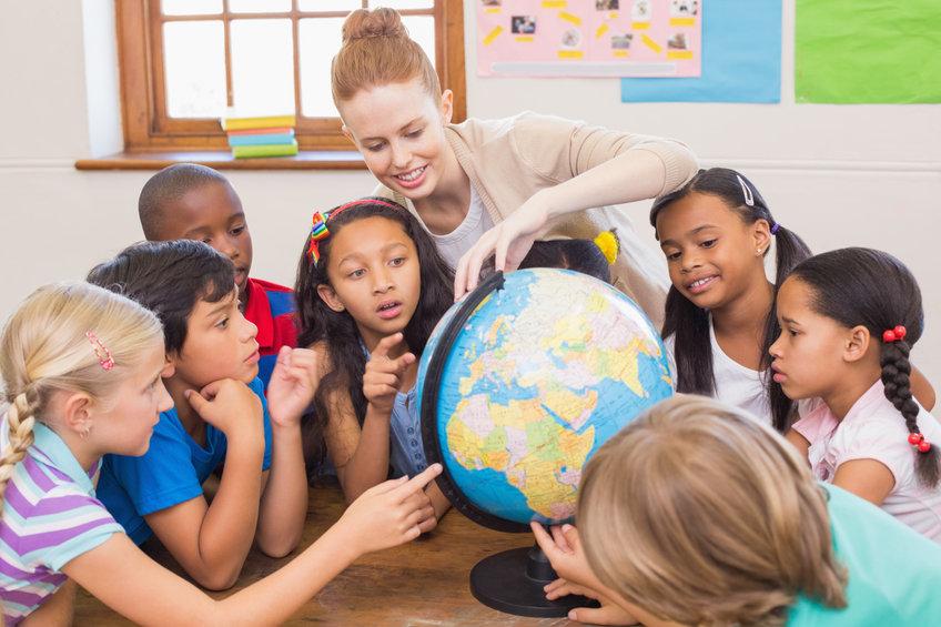 Des enfants en programme scolaire international regardent une mapmonde