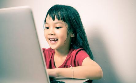 Enfant souriant face à son ordinateur sur lequel elle prend son cours en ligne