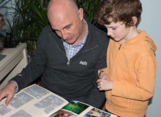 Un papa regarde un album photo avec son fils