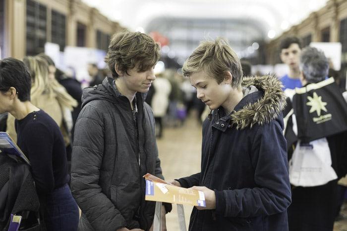 2 jeunes s'interrogent sur la brochure de L'Office pour choisir un séjour linguistique
