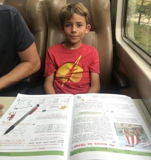 Un garçons fait ses devoirs de vacances Jules et Léonie
