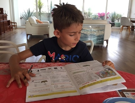 Un garçon révise sur son cahier de vacances