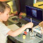 Un enfant fait de la peinture lors d'un atelier en ligne