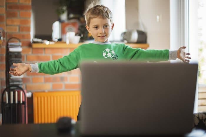 Un enfant s'amuse face à son écran lors d'un cours de français en ligne