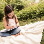 Une petite fille révise ses devoirs de vacances en français dans un jardin