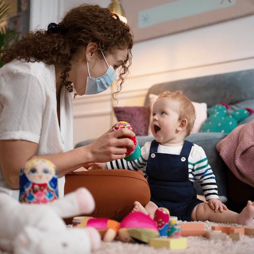 Une nounou portant un masque anti-Covid joue avec un bébé