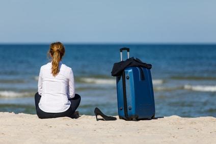 Une salariée réfléchit à sa mission solidaire, l'air rêveuse sur une plage