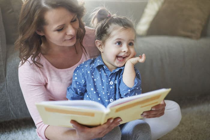 Une maman éveille la curiosité de sa fille en lui lisant un livre pour enfant