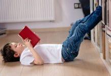 Un enfant prend plaisir à lire un livre allongé par terre