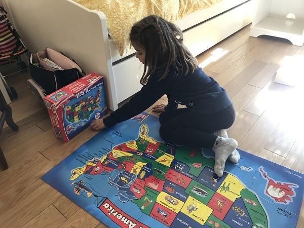 Une petite fille fait un puzzle avec sa nounou