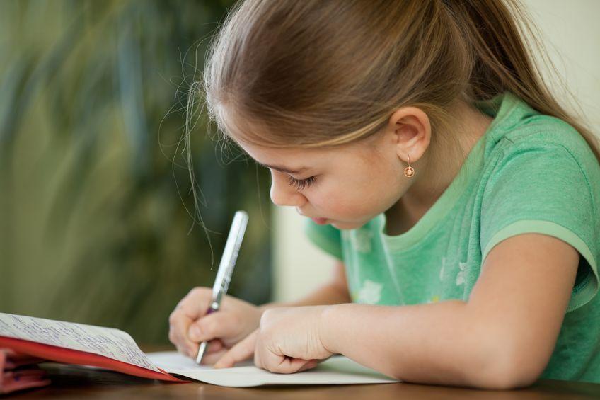 Une petite fille fait ses devoirs de CP du Cours Griffon