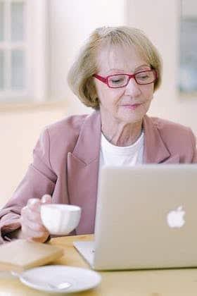 Une senior consulte son ordinateur pour ses cours de langue en ligne
