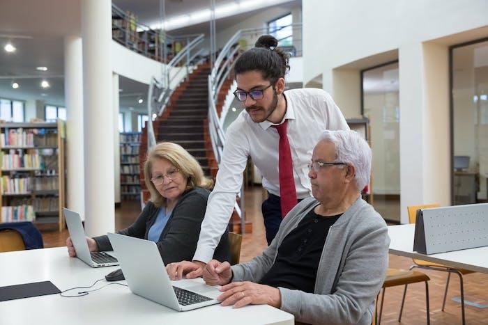 Des seniors se font aider à la médiathèque pour comprendre comment trouver un tandem linguistique