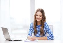 Une jeune femme suit une formation en langue en ligne en prenant des notes